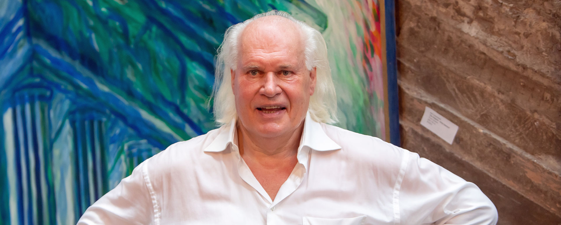 Rolf Lukaschewski posiert vor einem seiner Gemälde