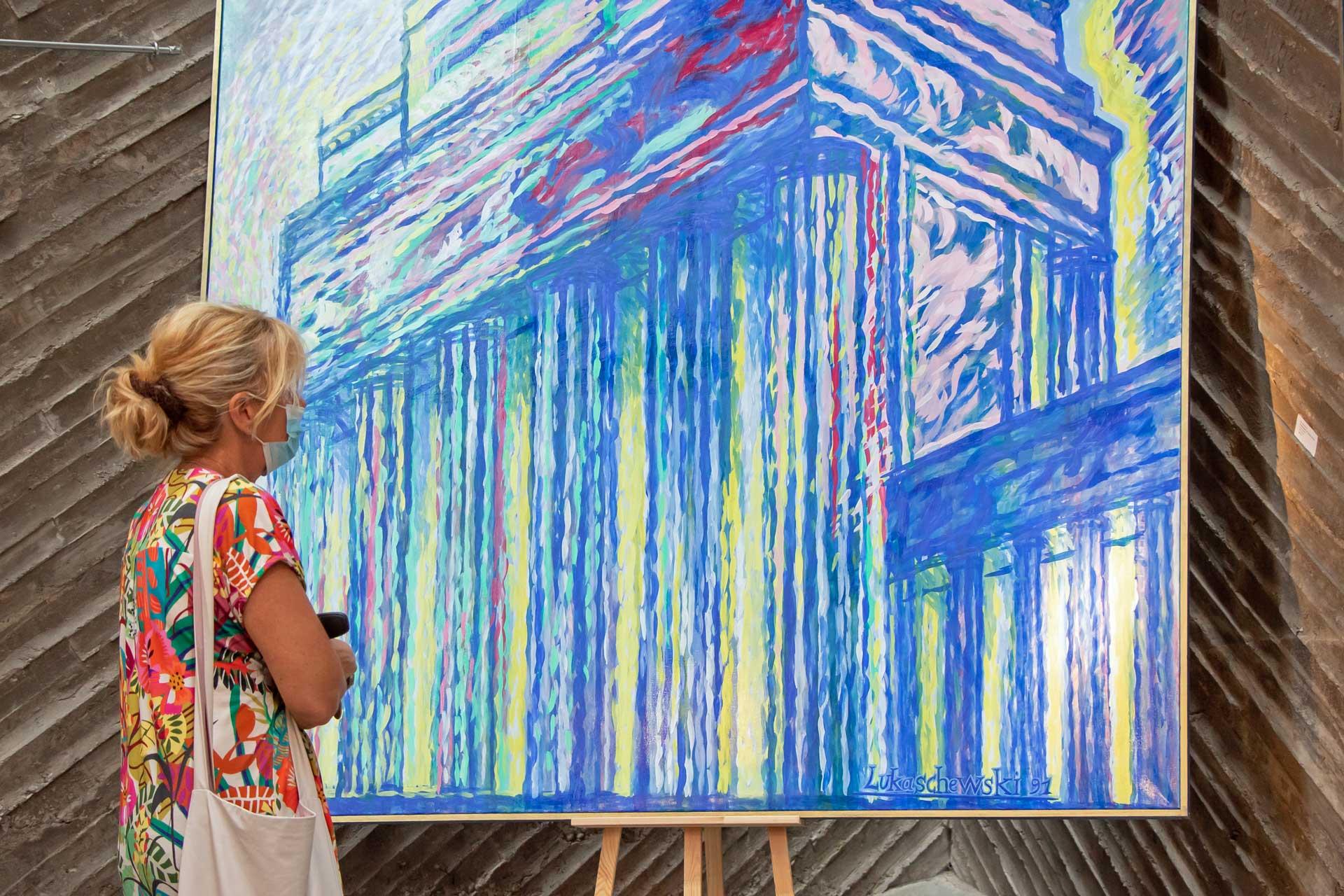Eine Frau betrachtet ein großformatiges Gemälde des Brandenburger Tors von Rolf Lukaschewski
